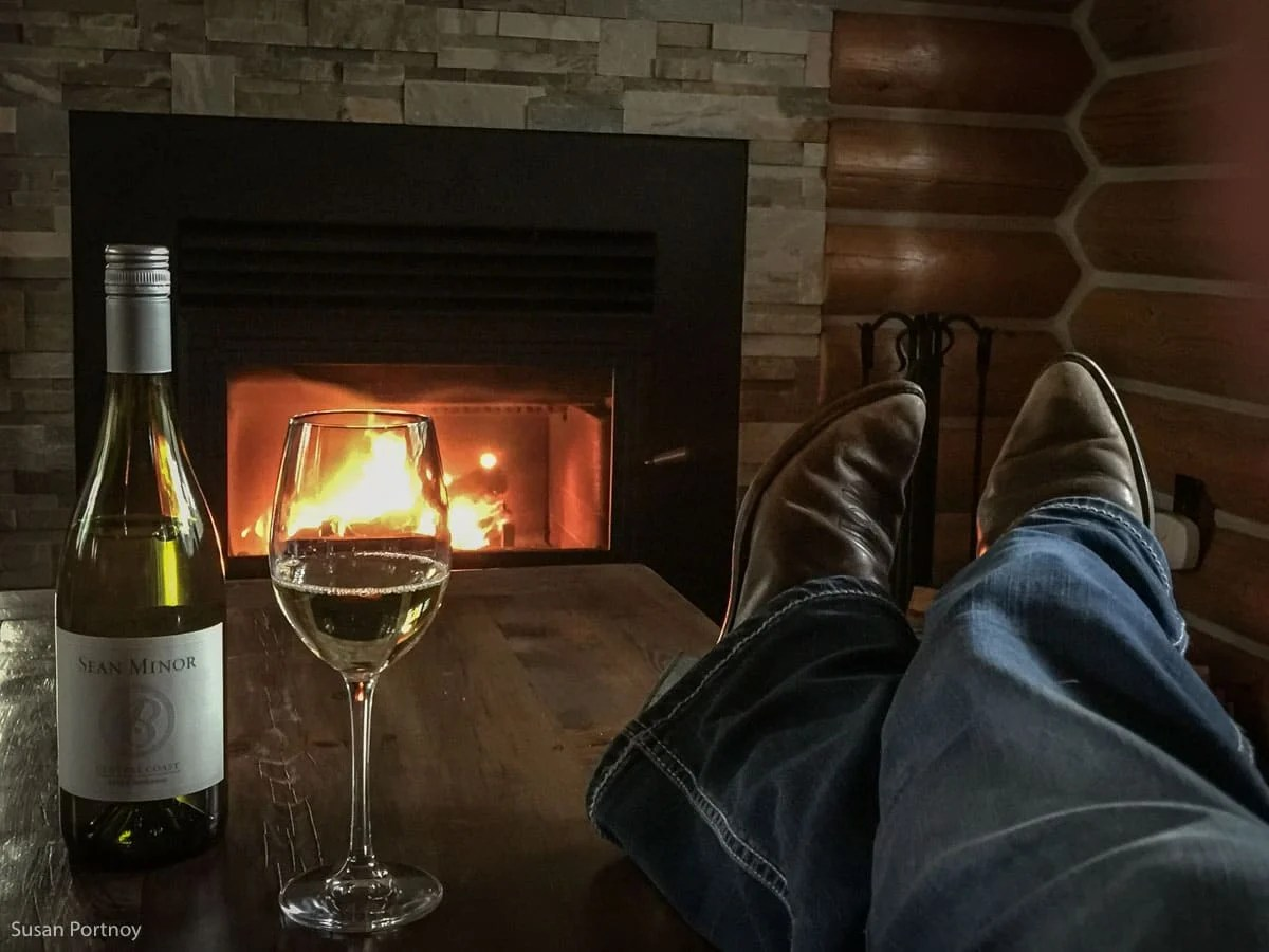 Cowboy boots on a coffee table with a bottle of wine in front of a fire.