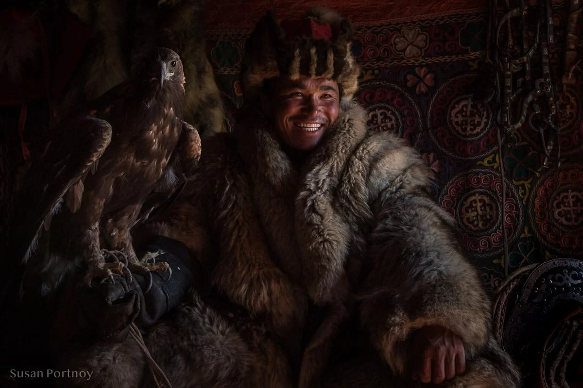 Sitting portrait of a Kazakh eagle hunter with his golden eagle wearing traditional winter fur coat and hat, Altai Mountains, Mongolia