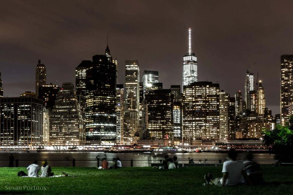 People on the lawn in Brooklyn Bridge Park sitting on blankets looking at the Manhattan skyline with the World Trade Center, WTC, in the background. New York City.