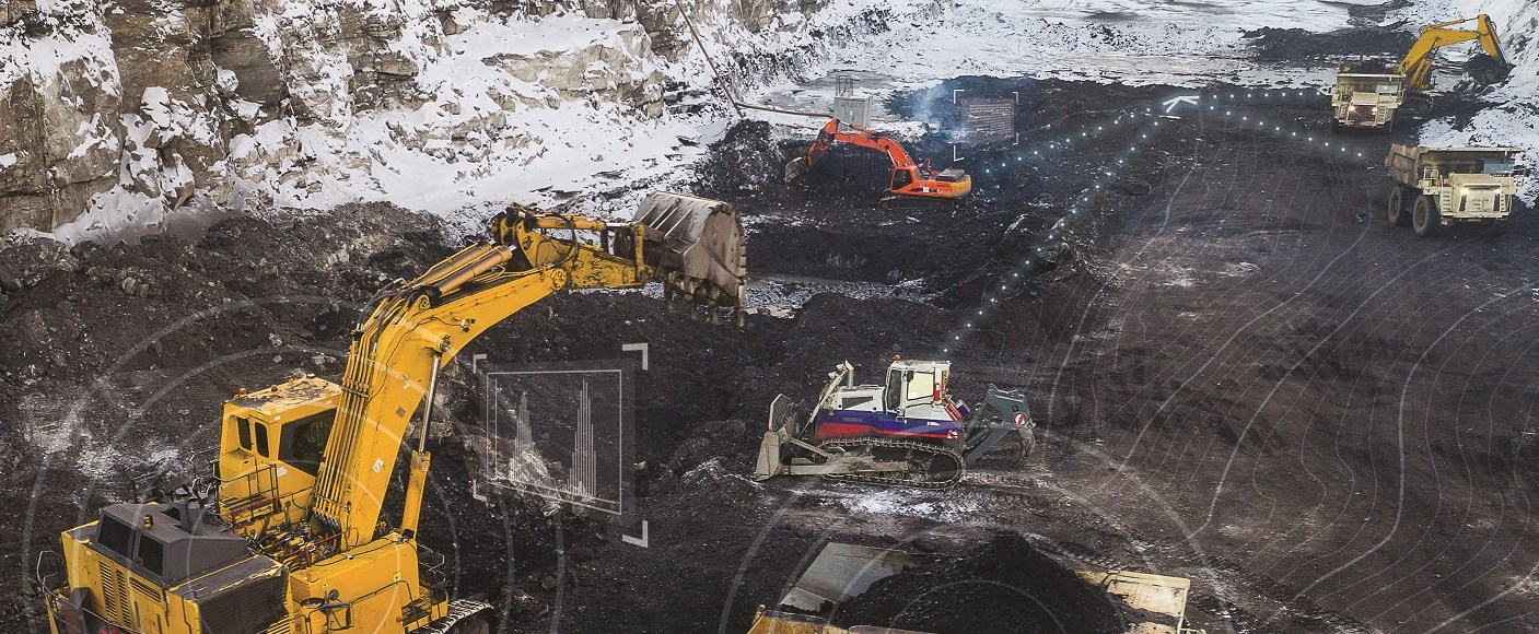 Mine trucks and excavators working together on a snowy mine site