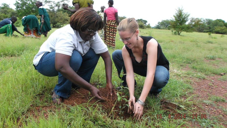Elizabeth Freele kneels next to a community stakeholder. Together they are planting a tree sapling