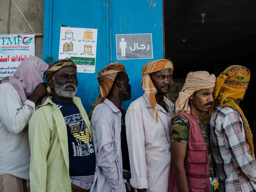 Yemeni men stand in line waiting for a weekly food distribution on April 23, 2018 in Al Fayoush, Yemen. Most of them are displaced from impoverished areas near the frontlines in Hudaydah and Taiz.