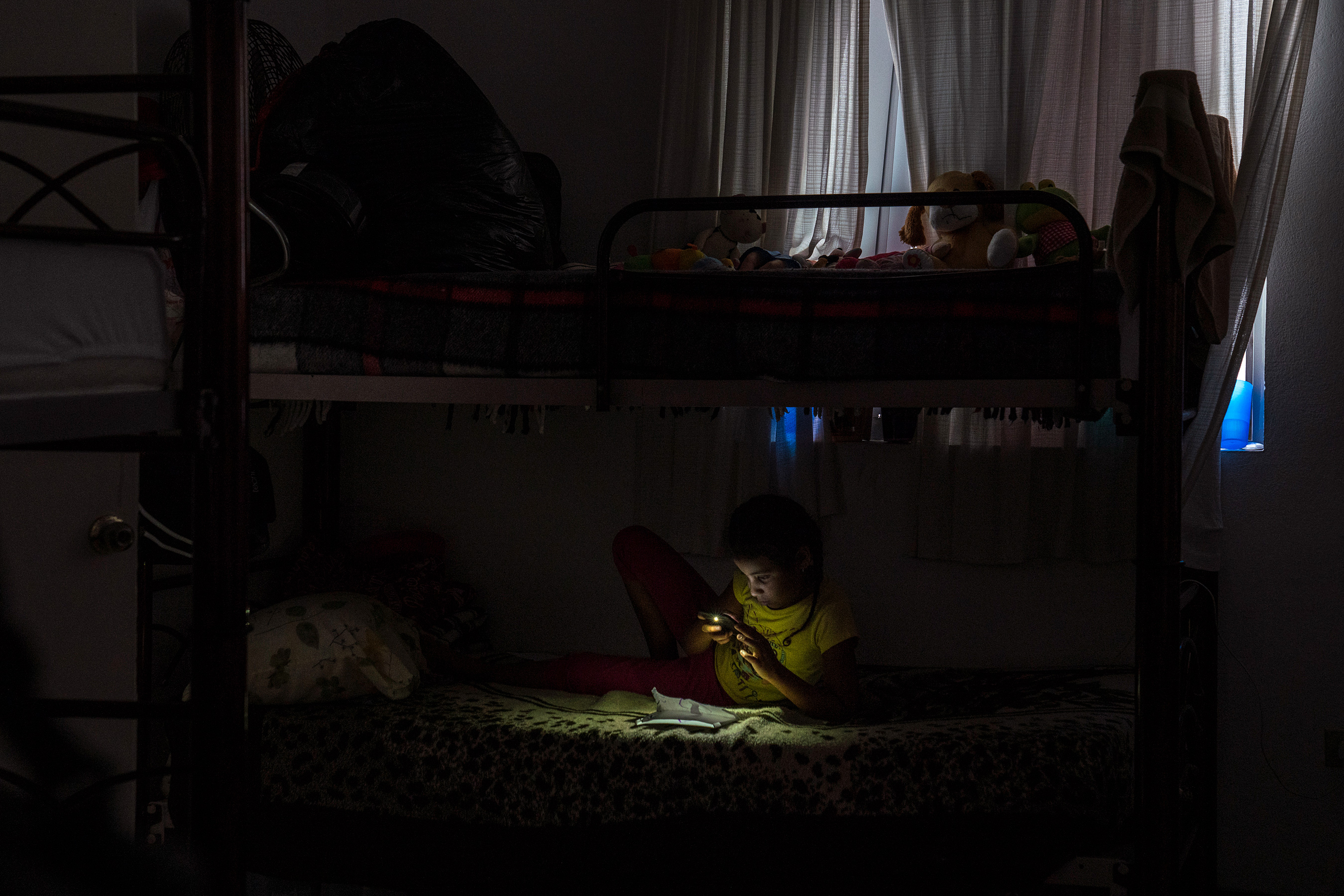 Nahomy, 7, from Honduras, plays with a cell phone in a shelter in Matamoros, Tamaulipas on Nov. 7, 2018. Her and her family have been waiting for weeks to seek asylum in the U.S. because Customs and Border Protection, CBP, agents have told them that they are at full capacity.Photo: Verónica G. Cárdenas for The Intercept