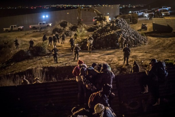 Asylum seekers from Honduras try to jump the border wall that divides U.S. and Mexico to enter US soil from Tijuana, while  activists from the US help them to do so, Jan. 01, 2019. (© Santi Palacios)