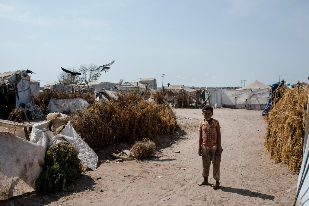 A Yemeni boy walks through the sand back to his tent on a hot morning on April 23, 2018 in Mishqafa Camp, Al Fayoush, Yemen. Most of the families come from impoverished areas near the frontline, and while the sheikh of the area claims NGOs have provided them with some assistance, the area is still destitute.