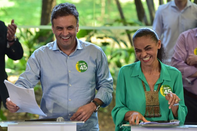 Brazil's presidential candidate for the Brazilian Social Democratic Party (PSDB), Aecio Neves (L), and former presidential candidate for the Brazilian Socialist Party's (PSB), Marina Silva, attend a campaign meeting in Sao Paulo on October 17, 2014. Neves lost to Brazilian President Dilma Rousseff in the first round almost two weeks ago, but opinion polls now show him in a statistical dead heat with her ahead of the October 26 run-off -- making Silva's backing vital. AFP PHOTO / NELSON ALMEIDA (Photo credit should read NELSON ALMEIDA/AFP/Getty Images)