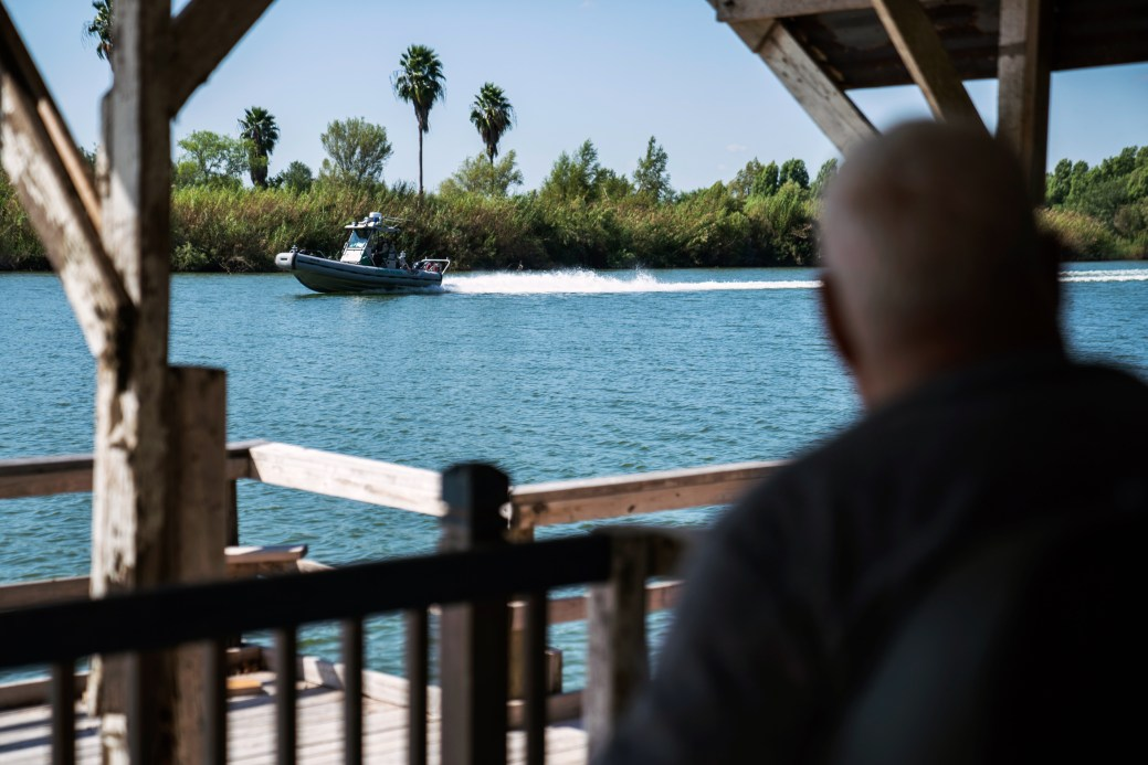 Fred Cabazos, 69, sits by the Rio Grande riverbank as a Border Patrol boat passes in Mission, Tex. on Nov. 6, 2018. Photo: Verónica G. Cárdenas for The Intercept