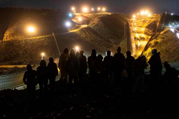 TOPSHOT - Central American migrants stand on a mound before attempting to cross from Tijuana to San Diego in the US on New Year's Eve, as seen from Tijuana, Baja California state, Mexico on December 31, 2018. - Around 100 Central American migrants made a failed attempt on New Year's Eve to cross over from Mexico into the United States. As night fell and people on both sides of the frontier prepared to celebrate New Year's Eve, the migrants tried to cross over but at least two smoke bombs were hurled and they ultimately held back. (Photo by Guillermo Arias / AFP)(Photo credit should read GUILLERMO ARIAS/AFP/Getty Images)