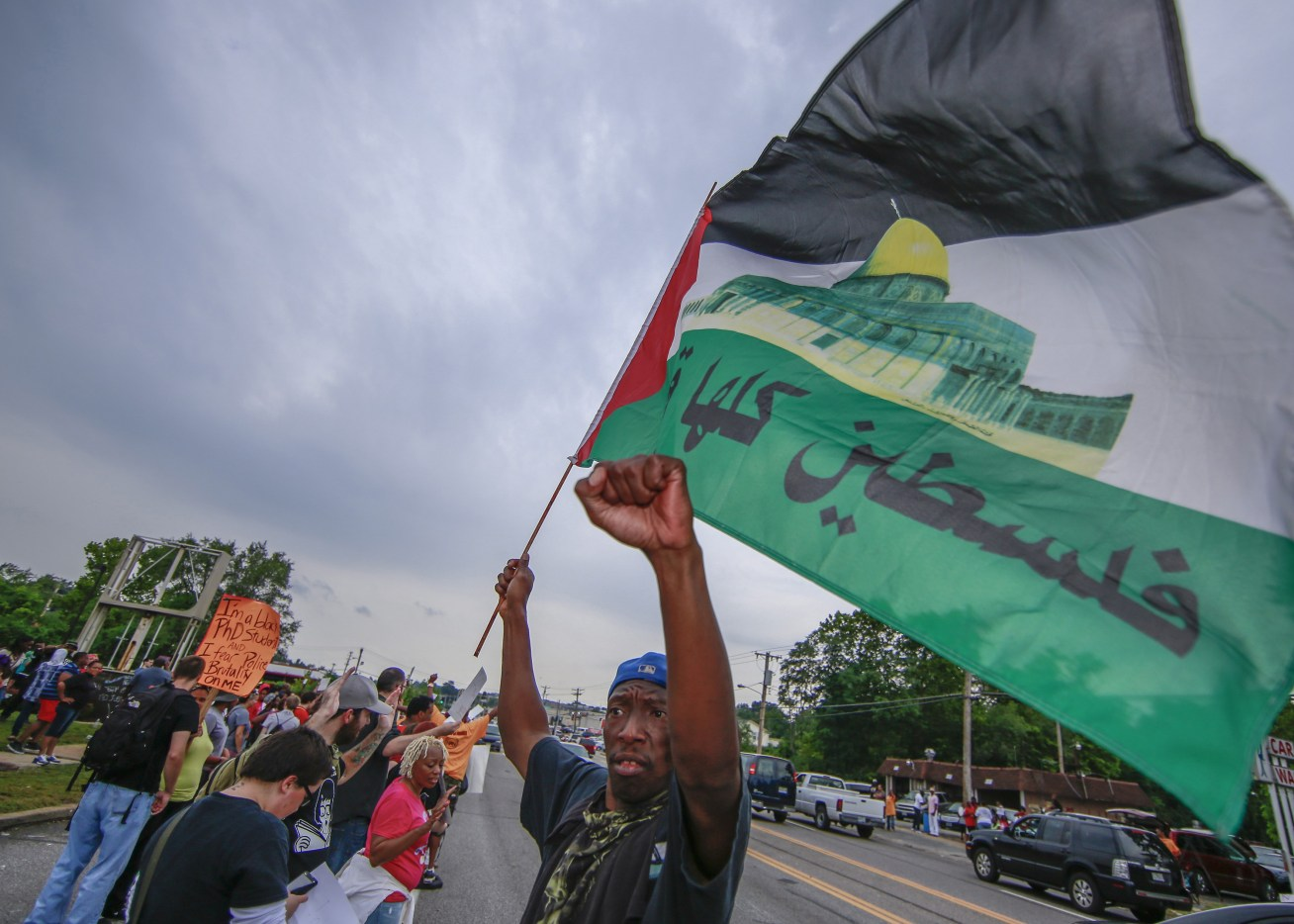 FERGUSON, UNITED STATES - AUGUST 16:  A protester waves Palestinian flag in solidarity with Gaza as Americans shout slogans and hold banners during a demonstration against the death of eighteen-year-old unarmed teen Michael Brown in Ferguson, Missouri on August 16, 2014. Brown, allegedly stole some cigars, shot dead by police in the St. Louis suburb of Ferguson, Missouri on August 09, 2014. (Photo by Bilgin Sasmaz/Anadolu Agency/Getty Images)