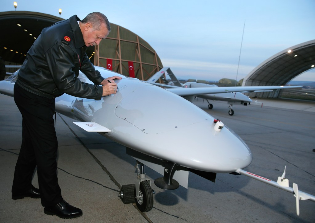 Turkey's President Recep Tayyip Erdogan signs a drone at a military airbase in Batman, Turkey, Saturday, Feb. 3, 2018. The Turkish military says two of its soldiers have been killed in Syria and a third was killed on the Turkish side of the border in an attack by Syrian Kurdish militiamen, saying Saturday's deaths were related to Turkey's operation against the Syrian Kurdish-held enclave of Afrin. (Murat Cetinmuhurdar/Pool Photo via AP)