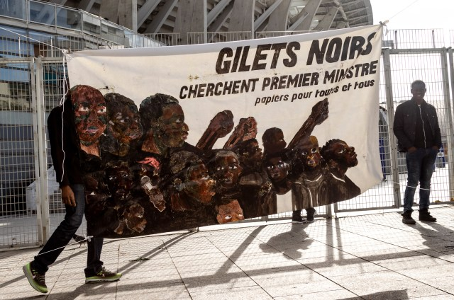 """A banner reads, """"Black Vests seeking the Prime Minister. Papers for everyone."""" at the Gilet Noirs protest outside of Charlety Stadium. The neutral meeting place where negotiations with Elior, a catering company that employs undocumented migrants, were discussed, Friday, Oct. 11, 2019. (Emma Francis/The Intercept)"""