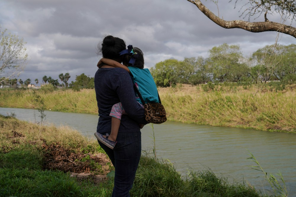 """Rocio carries her four-year-old daughter, Patricia, in an encampment where they live in Matamoros, Mexico on Feb. 23, 2020. The following day Rocio and her family were sent back to Mexico after their court hearing. They were kidnapped for two months the first time they were sent back under the """"Remain in Mexico"""" program to wait for their asylum case to be decided last year.Verónica G. Cárdenas for The Intercept"""