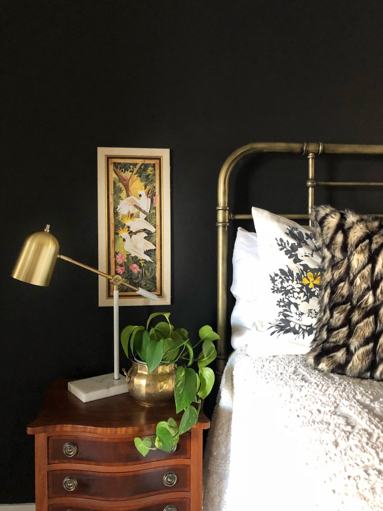 An Eclectic '70s Home Filled With Vintage Finds - Jenasie Earl | Bedroom with dark walls are lifted by adding pops of pattern and colour as well as texture. Vintage lighting and art add detail and interest.