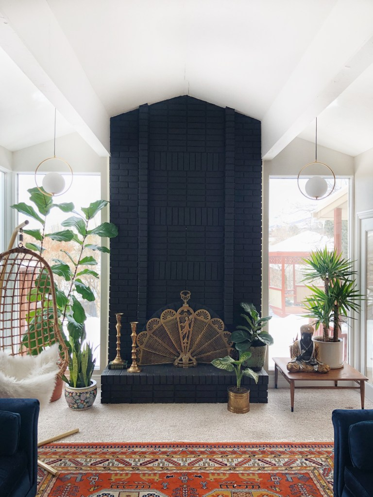 An Eclectic '70s Home Filled With Vintage Finds - Jenasie Earl | An eclectic living room filled with light and made unique with vintage finds. Double height windows and a dramatic black fireplace add substance to the living room.