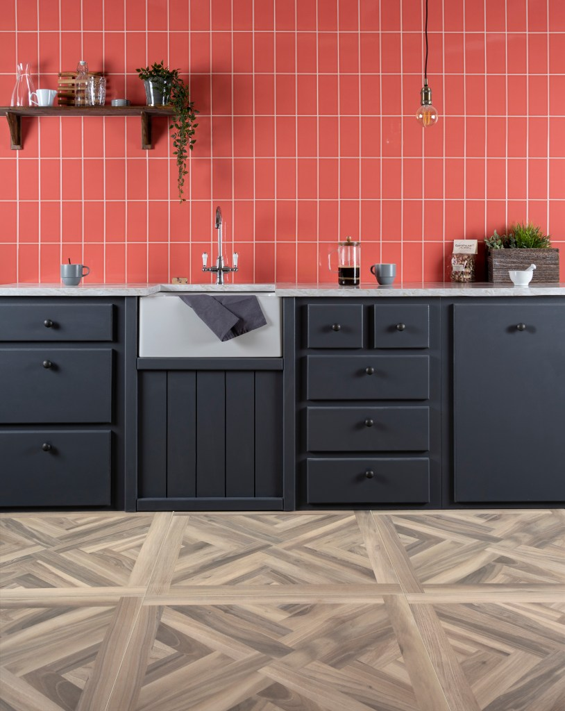The Versatile Brick Tile & How To Use It | Laying your tiles vertically is a great eye catching contemporary alternative way to adorn your kitchen walls. These on trend living coral craquelure tiles from Walls and Floors look fantastic paired with a darker style kitchen.