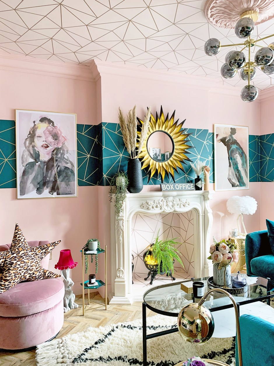 Pink and teal living room that uses patterned wallpaper to the ceiling (fifth wall) to create interest and the unexpected.