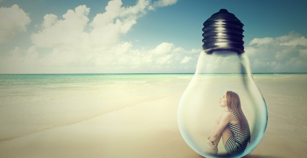 Girl sitting in a lightbulb feeling failure