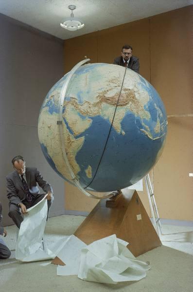 Smithsonian Observatory scientists Fred Whipple and J. Allen Hynek plotting orbit of Sputnik I on globe at MIT - 1957