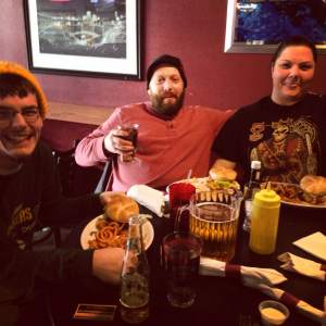 Three very happy Green Bay Packers fans. Their team won and they had gigantic burgers and pitchers to celebrate their victory in Ice Bowl II. Let the curly fries rain up in hear! At Scorz Bar and Grill in Mount Vernon, IA.