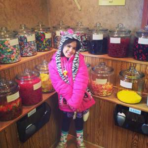 Gigi taking time for her famous pose in front of the massive variety of candy at The Shameless Chocoholic in LeClaire.