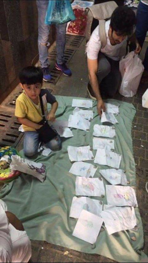 Muslim child is selling his simple drawings