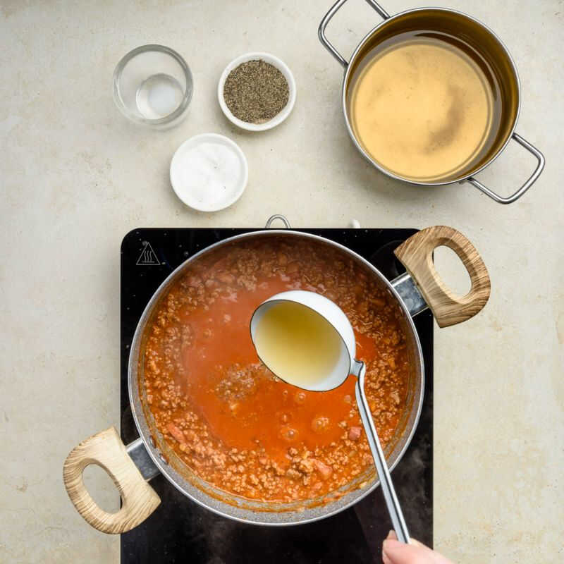 Ragù, bolognese sauce, with a ladle of hot broth