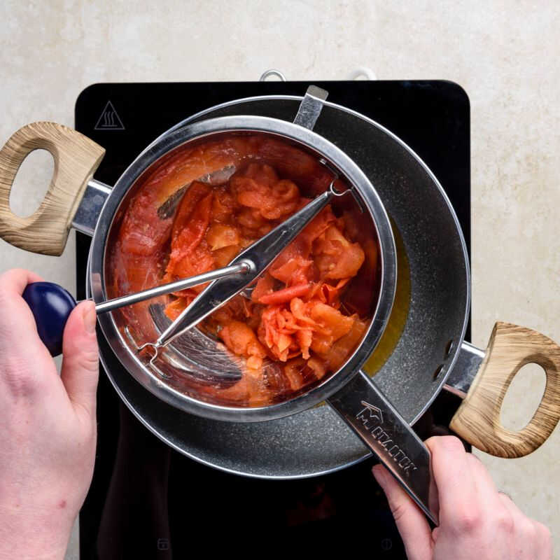 Once cooked, transfer the tomatoes to a food mill placed over a saucepan
