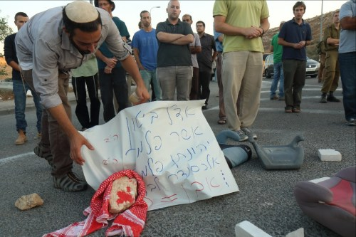 Photo: Hillel Maeir, Tazpit News Agency / An Israeli man holds a sign with names: Adele Biton, Asher Palmer, Jonathan Palmer, and Alexander Levlovitz, all victims of Palestinian rock attacks on the road.