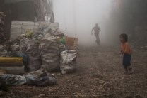 29: FEAR OF THE UNKNOWN. A child is seen crying alone as his brother come running towards him through thick fog to comfort and ease the cries at the dump-site area in Barangay Irisan in Baguio City.