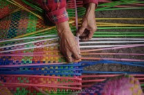 13: Rose Balansag, 65yrs old, weaving a huge floor mat out of discarded plastic drinking straws along Bonifacio Street in Baguio City.