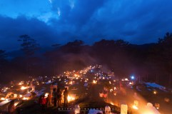 """29: FIRE FOR THE DEAD. The people of Sagada, Mountain Province, gather in a cemetery for """"Panag-apoy"""" (to make fire) at dusk on Thursday, All Saints' Day. Combining Filipino practices with Anglican church rites, the ritual is intended to give warmth to the souls of the departed."""