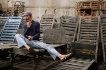 """A """"komboy"""" or """"baggage boy"""" gestures as he takes a break on a pile of large wooden trolley at the public market in Baguio City."""
