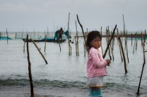 Marianne waits for her father at the beach of Santa Ana in Cagayan as they fix up the fishing nets and poles to catch baby eels.