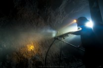 A miner uses a air-pressured hand drill to take out gold ores 1,500 meters below at a mining shaft of Lepanto Mines in Benguet.