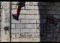 A boy's feet is seen hanging as he sits on top of a concrete wall trying to watch the Lang-ay Festival grand showdown in Bontoc, Mountain Province.