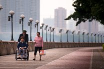Elderly people takes a walk along the park of Haixinsha in Guangzhou, China.
