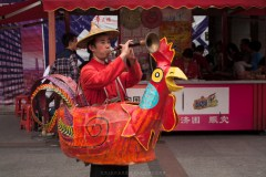 A man dressed up as a lucky chicken as he plays his trumpet to call people to buy candies from him at a public market in Guanghou, China.