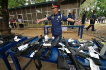 "Chief Supt. Benjamin Magalong, Cordillera police director, displays the weapons surrendered by politicians in Abra, Philippines, one of the ""areas of concern"" declared by the Commission on Elections for their history of election violence. The guns will be muzzled and kept at Camp Juan Villamor in the provincial capital of Bangued as the Comelec imposes a gun ban during the midterm elections."