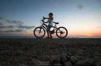 During sundown, a boy cycles on top of a concrete barrier along the beach of Mina De Oro in Vigan City, Ilocos Sur.