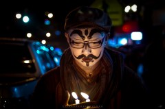 Performing artist Rey Angelo Aurelio is seen with candles along the traffic in Session Road in Baguio City at night.