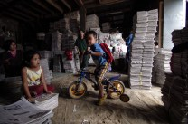 Young siblings are seen playing inside a newspaper recycling depot at Brgy. Pico in La Trinidad, Benguet as their parent working to cut newspapers in to half and pack them into bundles and are sold for P70 ($1.50 USD) per bundle to vegetable dealers to be used for packaging Benguet vegetables.
