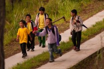 Children, along with their gardening tools, walks along a tire-path near a mining area in Mankayan in Benguet after their school hours.