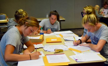 Some more of Villanova University's women's field hockey team writng letters to Philadlephia area schools suggesting a sock drive for the homeless as a school community service project.