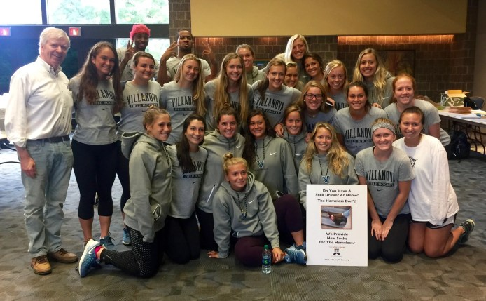 Members of Villanova University's women's field hockey team, and Tom Costello, Jr, Chief Sock Person, The Joy of Sox. The students put together a personalized letter and package to be sent to Philadelphia area schools suggesting they hold a sock drive for the homeless as a school community service project. (note the two basketball players in the background)
