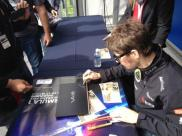 Why is Romain signing a laptop?