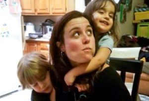 Reluctant parent with kids hanging off her