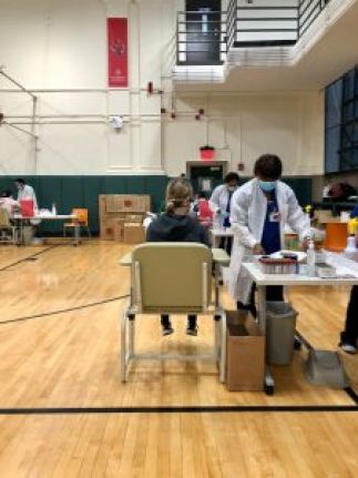 Woman getting a blood test in a gymnasium