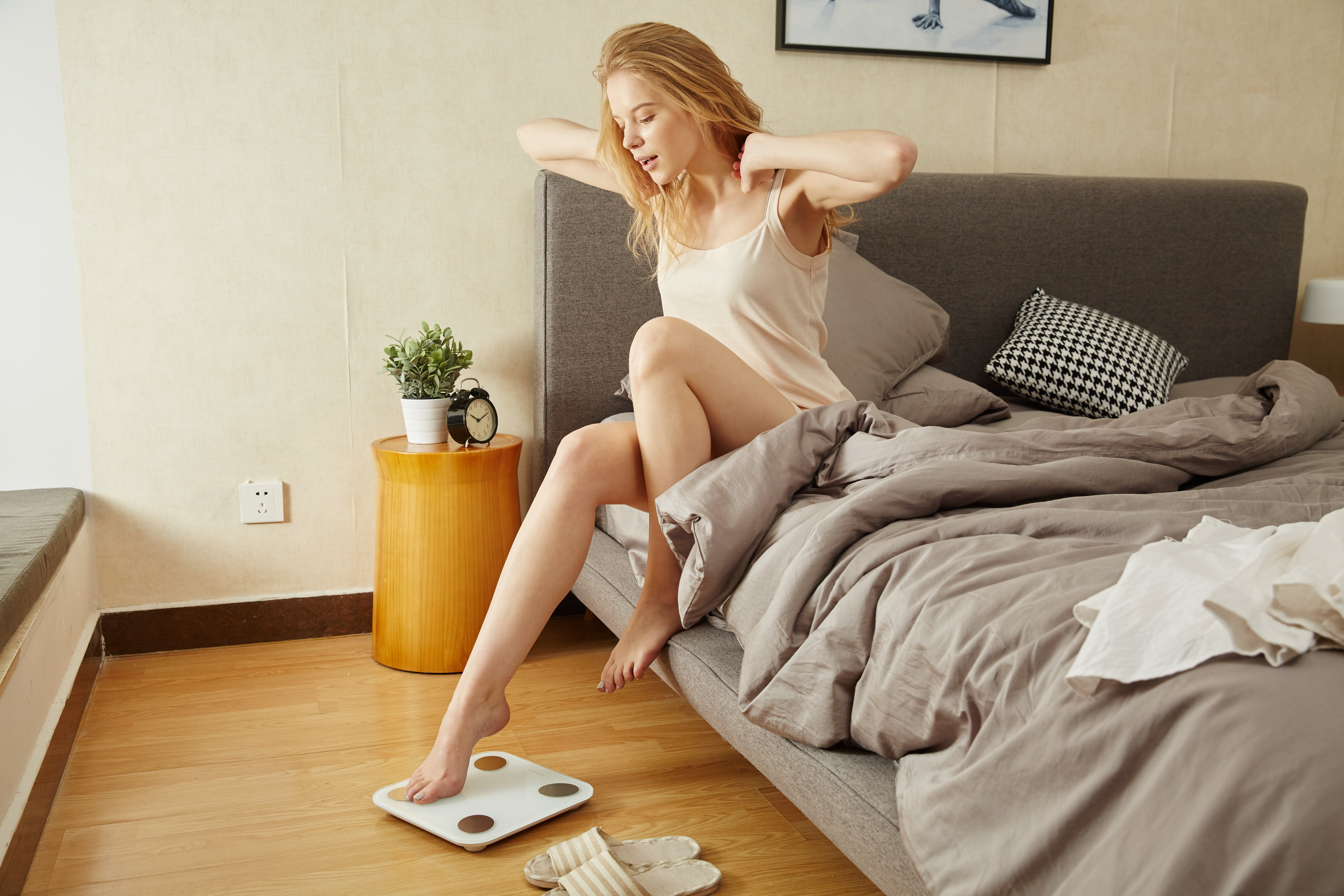 An image for Boise weight loss, a woman gingerly measures her weight by placing a toe on the scale.
