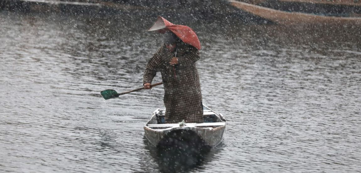 Holding his 'nearly breaking down umbrella', a boatman pulls his Shikara on Dal…