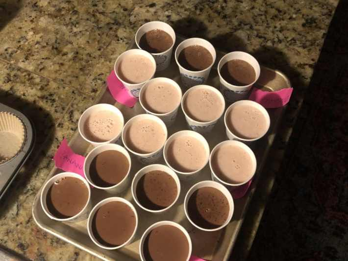 Dixie cups filled with popsicle samples on dark granite counter top. kitchen counter scene